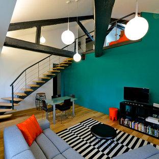 Inspiration pour une grande salle de séjour design avec un sol en bois brun, un téléviseur indépendant et un mur multicolore.