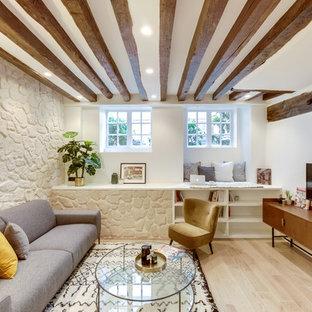 Cette photo montre une salle de séjour chic avec un mur blanc, un sol en bois clair, aucune cheminée, un téléviseur fixé au mur et un sol beige.