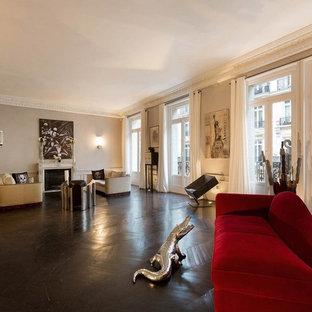 Idée de décoration pour une très grand salle de séjour design ouverte avec un mur beige, un sol en bois foncé, une cheminée standard et un manteau de cheminée en pierre.