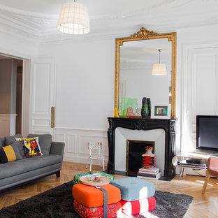 Idée de décoration pour une salle de séjour tradition fermée et de taille moyenne avec un mur blanc, un sol en bois clair, une cheminée standard, un manteau de cheminée en pierre et un téléviseur indépendant.