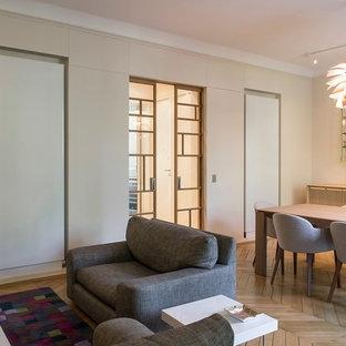 Réalisation d'une salle de séjour design avec un mur beige et un sol en bois brun.