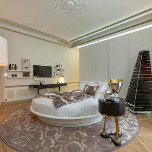 Idée de décoration pour une salle de séjour design avec un mur beige, un sol en bois clair et un téléviseur fixé au mur.