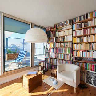 Cette photo montre une salle de séjour avec une bibliothèque ou un coin lecture chic de taille moyenne et fermée avec un sol en bois clair.