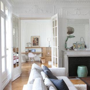 Inspiration pour une salle de séjour design fermée avec un mur blanc, un sol en bois brun et une cheminée standard.