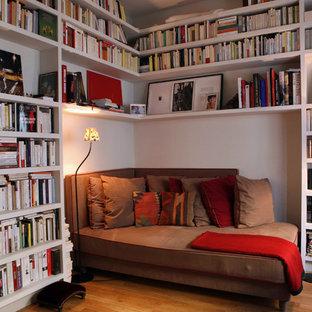 Cette image montre une salle de séjour avec une bibliothèque ou un coin lecture design de taille moyenne avec un mur blanc et un sol en bois brun.