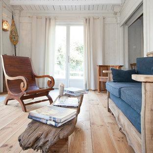 Exemple d'une salle de séjour éclectique de taille moyenne et fermée avec un mur blanc et un sol en bois brun.