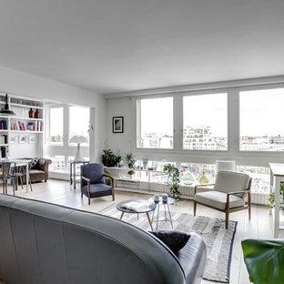 Inspiration pour une salle de séjour nordique ouverte avec un mur blanc, un sol en bois clair et un sol beige.
