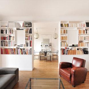 Inspiration pour une salle de séjour avec une bibliothèque ou un coin lecture bohème de taille moyenne et fermée avec un mur blanc, un sol en bois brun, aucune cheminée et aucun téléviseur.