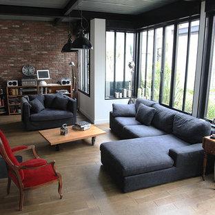 Aménagement d'une salle de séjour industrielle de taille moyenne et ouverte avec un mur blanc et un sol en bois brun.