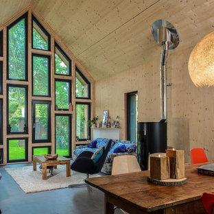 Idées déco pour une salle de séjour contemporaine avec un mur beige, béton au sol et un manteau de cheminée en métal.
