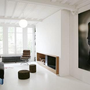 Exemple d'une salle de séjour tendance avec un mur blanc, une cheminée standard, un manteau de cheminée en plâtre et un sol blanc.