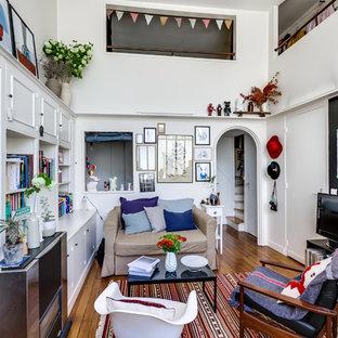 Cette photo montre une salle de séjour avec une bibliothèque ou un coin lecture éclectique de taille moyenne avec un mur blanc, un sol en bois brun et un téléviseur indépendant.