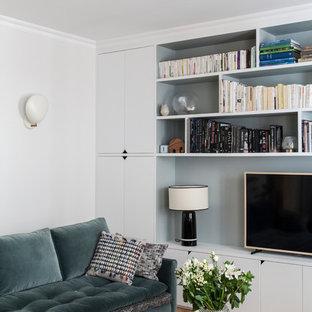 Idée de décoration pour une petite salle de séjour avec une bibliothèque ou un coin lecture nordique avec un mur blanc, un sol en bois clair, un téléviseur indépendant et un sol beige.