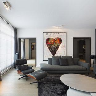 Exemple d'une grande salle de séjour éclectique ouverte avec un mur blanc, un sol en bois clair, une cheminée standard et un téléviseur dissimulé.