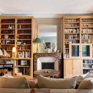Cette photo montre une salle de séjour avec une bibliothèque ou un coin lecture chic de taille moyenne et fermée avec un mur blanc, un sol en bois brun, une cheminée standard, un manteau de cheminée en pierre et un téléviseur dissimulé.