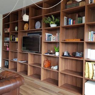 Cette photo montre une grande salle de séjour avec une bibliothèque ou un coin lecture exotique ouverte avec un sol en bois clair, cheminée suspendue et un téléviseur indépendant.