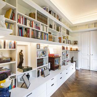 Cette photo montre une grande salle de séjour avec une bibliothèque ou un coin lecture chic avec un mur blanc, un sol en bois foncé, aucune cheminée, aucun téléviseur et un sol marron.