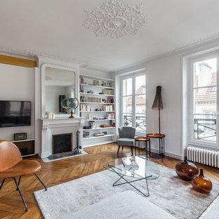 Aménagement d'une grande salle de séjour avec une bibliothèque ou un coin lecture contemporaine fermée avec un mur blanc, un sol en bois clair, une cheminée standard, un téléviseur fixé au mur et un manteau de cheminée en plâtre.