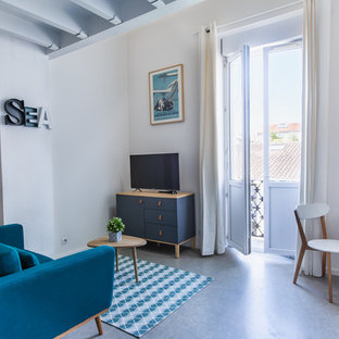 Exemple d'une salle de séjour bord de mer ouverte et de taille moyenne avec un mur blanc, béton au sol, un téléviseur indépendant et un sol gris.