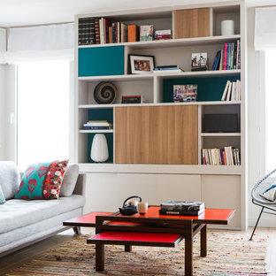 Réalisation d'une salle de séjour design ouverte avec un sol en bois clair, un téléviseur dissimulé, un mur blanc et un sol beige.