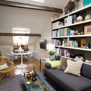 Aménagement d'une salle de séjour avec une bibliothèque ou un coin lecture éclectique de taille moyenne avec un mur blanc, un sol en bois brun et un téléviseur fixé au mur.