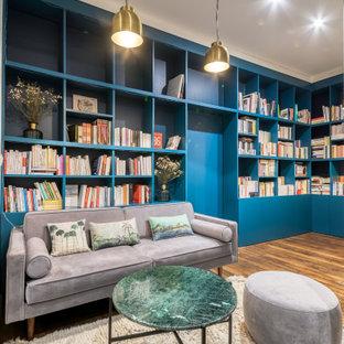 Cette photo montre une salle de séjour avec une bibliothèque ou un coin lecture tendance de taille moyenne et ouverte avec un mur bleu, un sol en bois brun, aucune cheminée, aucun téléviseur et un sol marron.