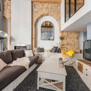 Imagen de sala de estar con barra de bar cerrada, urbana, de tamaño medio, con paredes azules, chimenea tradicional y televisor independiente
