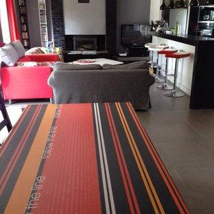 パリの中サイズのコンテンポラリースタイルのおしゃれなファミリールーム (ホームバー、グレーの壁、セラミックタイルの床、標準型暖炉、レンガの暖炉まわり、コーナー型テレビ、グレーの床) の写真