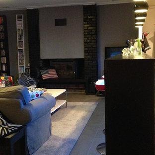 パリの中くらいのコンテンポラリースタイルのおしゃれなオープンリビング (グレーの壁、セラミックタイルの床、標準型暖炉、レンガの暖炉まわり、コーナー型テレビ、グレーの床) の写真
