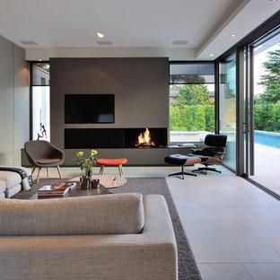 Réalisation d'une grand salle de séjour design fermée avec un mur gris, une cheminée ribbon et un téléviseur encastré.