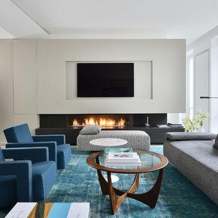 Aménagement d'une grande salle de séjour contemporaine ouverte avec un mur blanc, une cheminée ribbon et un téléviseur fixé au mur.