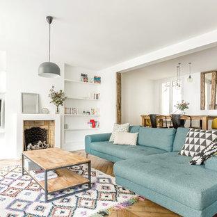 Exemple d'une salle de séjour scandinave ouverte et de taille moyenne avec un mur blanc, un sol en bois clair, une cheminée standard et un téléviseur fixé au mur.