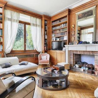 Cette photo montre une salle de séjour avec une bibliothèque ou un coin lecture chic avec un mur marron, un sol en bois clair, une cheminée standard, un manteau de cheminée en pierre, un téléviseur indépendant et un sol marron.