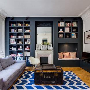 パリの大きいコンテンポラリースタイルのおしゃれな独立型ファミリールーム (ライブラリー、無垢フローリング、標準型暖炉、据え置き型テレビ、マルチカラーの壁) の写真