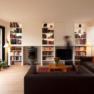 パリの中くらいのコンテンポラリースタイルのおしゃれなオープンリビング (ライブラリー、白い壁、淡色無垢フローリング、据え置き型テレビ) の写真