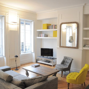 Aménagement d'une salle de séjour avec une bibliothèque ou un coin lecture contemporaine de taille moyenne et ouverte avec un mur blanc, un sol en bois brun et un téléviseur indépendant.