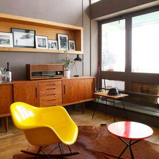 Idées déco pour une salle de séjour rétro avec un mur gris et un sol en bois clair.