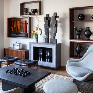 Cette image montre une salle de séjour design avec un mur blanc, un sol en bois brun, une cheminée standard, un manteau de cheminée en béton et un téléviseur fixé au mur.