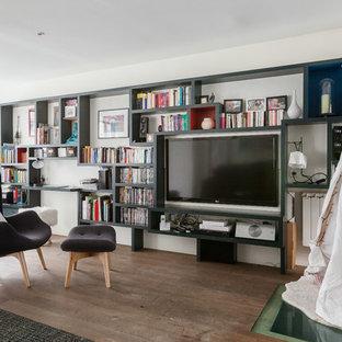Réalisation d'une grande salle de séjour avec une bibliothèque ou un coin lecture design ouverte avec un mur blanc, un sol en bois brun, aucune cheminée et un téléviseur fixé au mur.