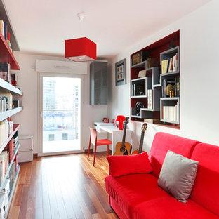 Inspiration pour une salle de séjour avec une bibliothèque ou un coin lecture design de taille moyenne et fermée avec un mur blanc, un sol en bois brun, aucune cheminée et aucun téléviseur.
