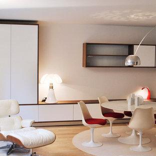 Cette image montre une grande salle de séjour design ouverte avec un mur blanc, un sol en bois clair et aucun téléviseur.