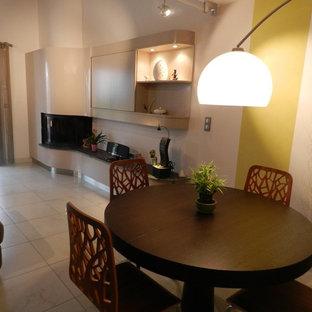 リヨンのコンテンポラリースタイルのおしゃれなファミリールーム (ベージュの壁、セラミックタイルの床、コーナー設置型暖炉、レンガの暖炉まわり、内蔵型テレビ) の写真