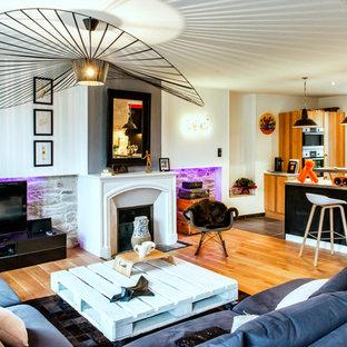 Cette image montre une salle de séjour bohème ouverte et de taille moyenne avec une cheminée standard, un téléviseur indépendant, un mur blanc, un sol en bois brun et un manteau de cheminée en béton.