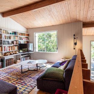 Aménagement d'une salle de séjour campagne avec un mur blanc, un sol en bois brun et un sol marron.
