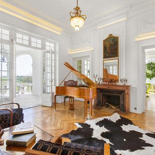 Idées déco pour une salle de séjour classique avec une salle de musique, un mur blanc, un sol en bois brun, une cheminée standard et un sol marron.