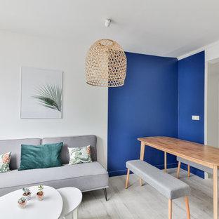 パリの中サイズの北欧スタイルのおしゃれなファミリールーム (青い壁、リノリウムの床、暖炉なし、据え置き型テレビ、ベージュの床) の写真