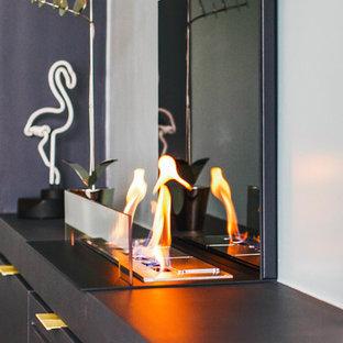 パリの中サイズのコンテンポラリースタイルのおしゃれなファミリールーム (ライブラリー、青い壁、淡色無垢フローリング、標準型暖炉、金属の暖炉まわり、据え置き型テレビ、ベージュの床) の写真