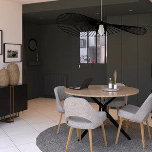 ナントの中サイズのコンテンポラリースタイルのおしゃれな独立型ファミリールーム (白い壁、セラミックタイルの床、コーナー設置型暖炉、石材の暖炉まわり、据え置き型テレビ、白い床) の写真