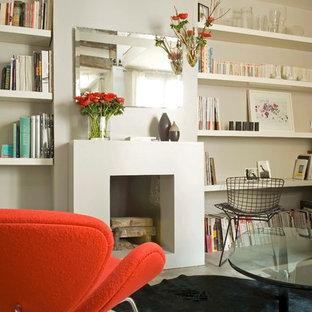 Cette photo montre une grande salle de séjour avec une bibliothèque ou un coin lecture tendance ouverte avec un mur blanc, béton au sol, une cheminée standard et un manteau de cheminée en béton.