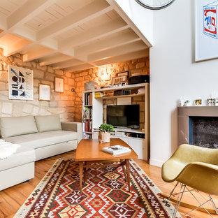 Inspiration pour une salle de séjour avec une bibliothèque ou un coin lecture bohème fermée et de taille moyenne avec un mur beige, un sol en bois clair, une cheminée standard, un manteau de cheminée en métal et un téléviseur encastré.